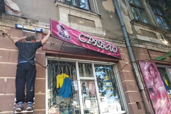 У центрі Тернополя з фасадів почали демонтувати рекламні вивіски