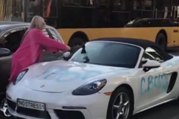 Білявка у центрі Києва сокирою розтрощила Porsche за 2 мільйони (Відео)